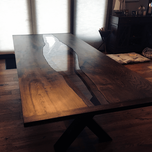 Angled view of raw edge table with inset glass set near a keepsake stand.