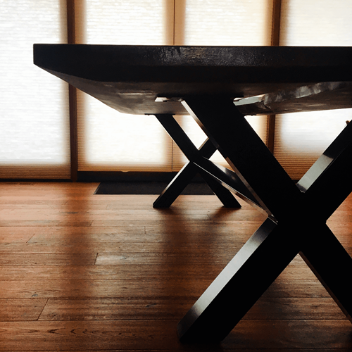 Dark end of table with custom fabricated metal legs.