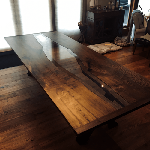Raw edge table with inset glass near lounge area.